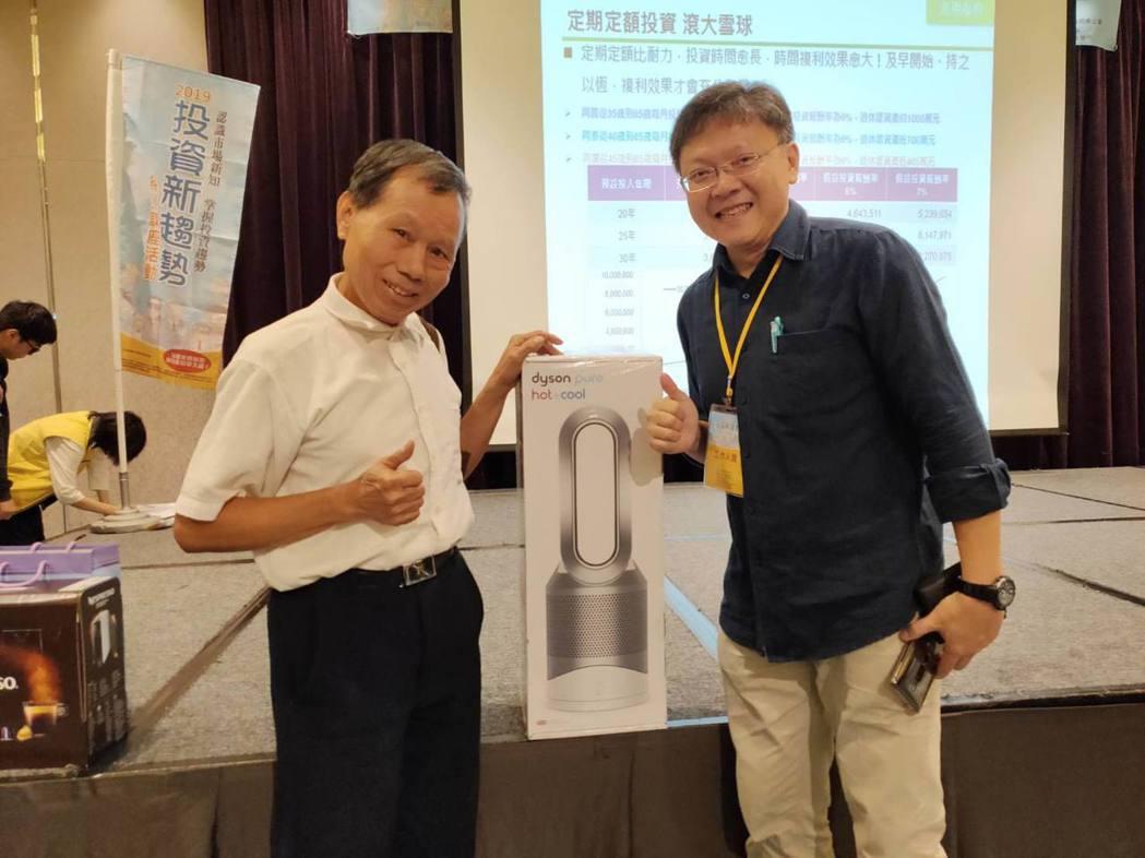 承辦單位證基會副處長林志光(右)與幸運抽中家電大獎的民眾開心合影。