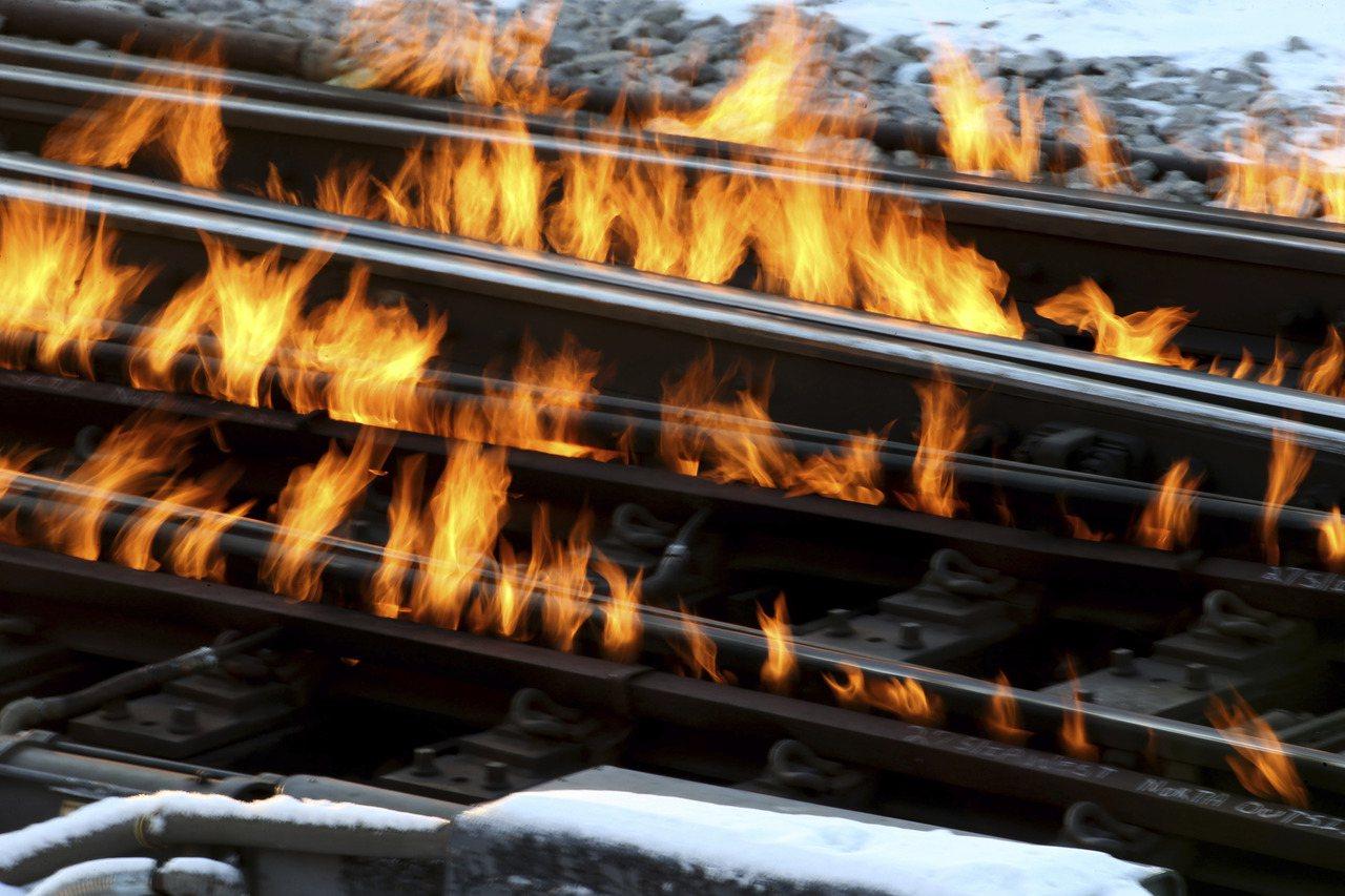 芝加哥部分火車鐵軌12日結冰,工人在軌道放火以使火車順利通行。(美聯社)