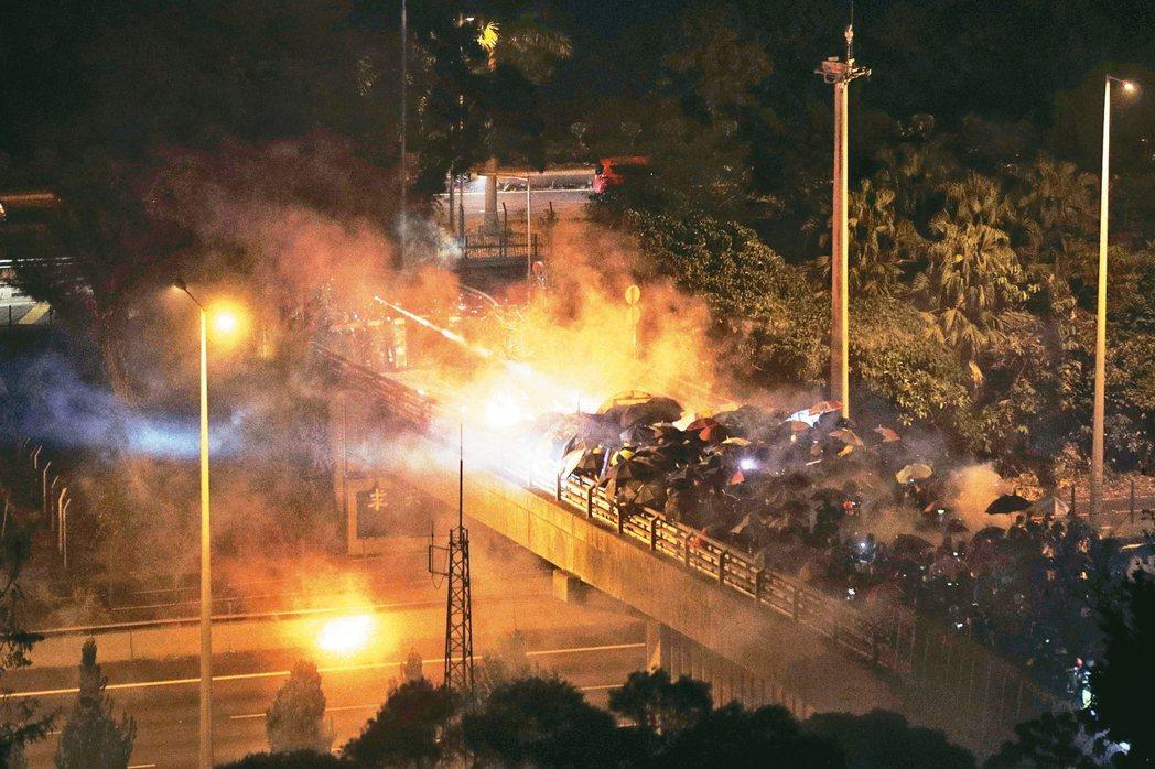 戴防毒面具的抗議者昨天在香港中文大學外頭與警方對峙,抗議群眾夜間在橋上和鎮暴警察...