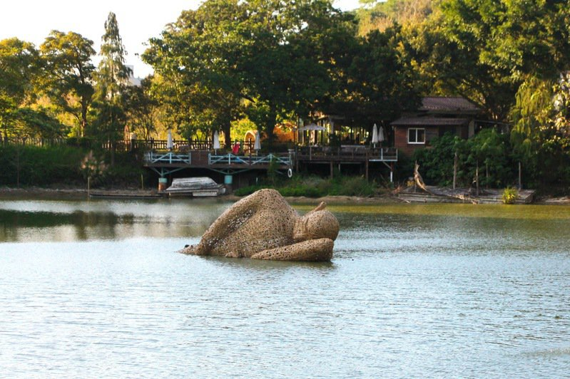 靜靜躺在湖中的沉睡巨人是作品「懶散時光」,以回收材料、廢棄物、竹子等材料打造而成,寓意是提醒觀看者,當人類過於懶散,忘記善待自然環境,或許有天終將被大自然給吞沒。記者陳斯穎/攝影
