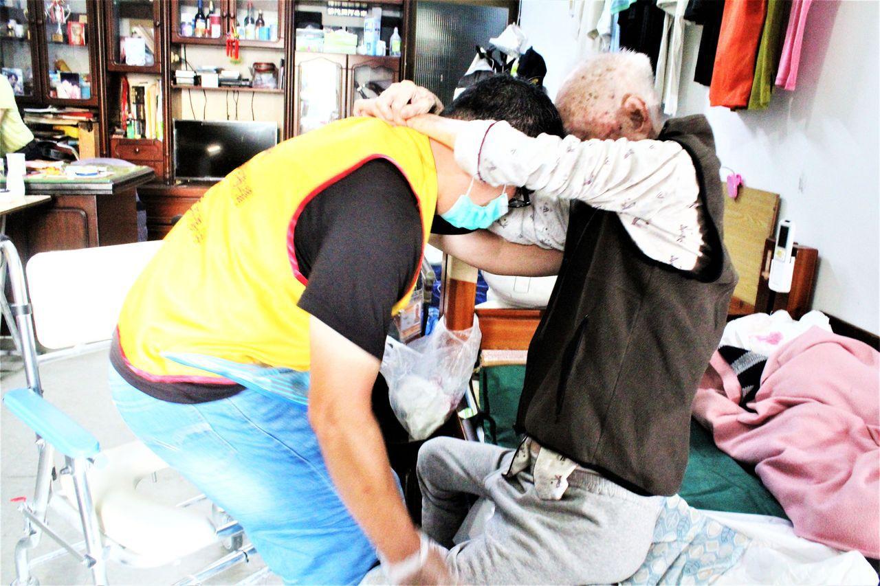 陳阿公(右)接受居家照顧服務,由居家服務人員(左)到宅,協助陳阿公從床上挪到便盆...