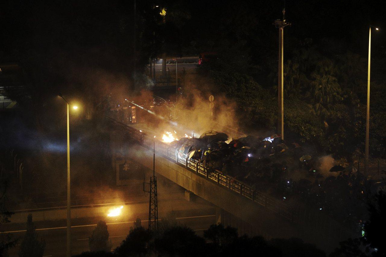 抗議群眾12日夜間在香港中文大學外的橋上和鎮暴警察對陣。美聯社