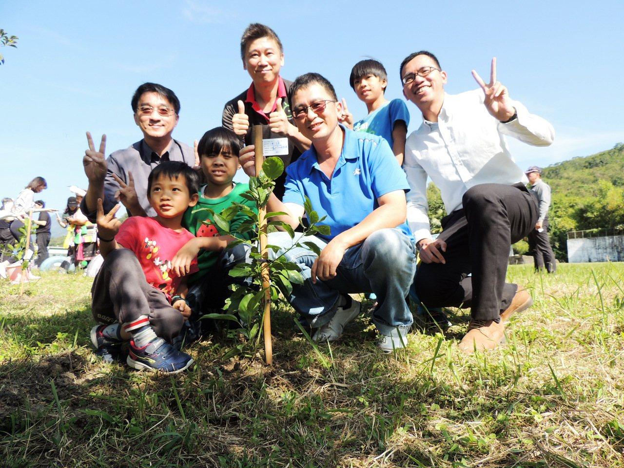 利吉分校的小朋友跟著來賓們開心的,合力種下牛樟樹苗。記者羅紹平/攝影