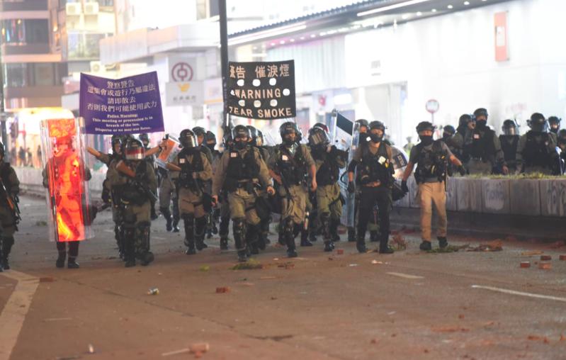 晚上9時許,仍有不少示威者在場聚集,一批手持警棍及盾牌的防暴警察在場舉起藍旗,並作出廣播。 圖/星島網