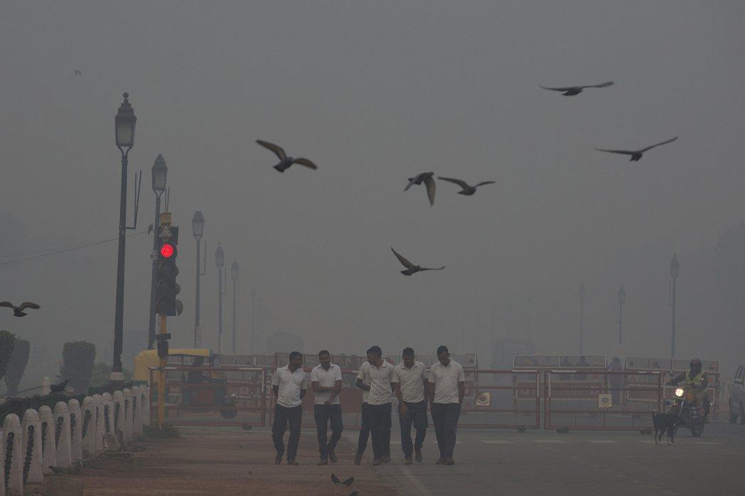 新德里街頭13日行人走在霧霾中。新華社