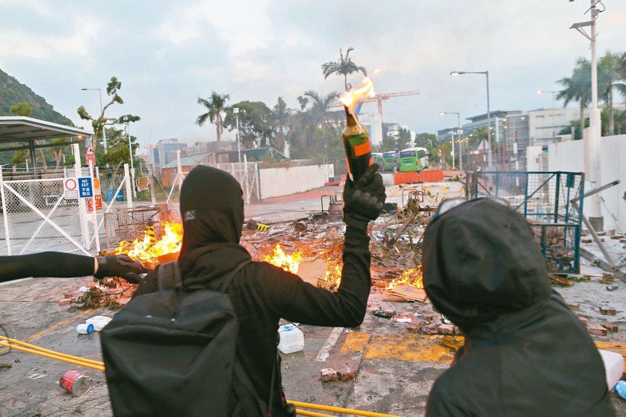 香港反送中示威者在香港中文大學與警方爆發激烈衝突,圖為示威者手持汽油彈與警方對峙...