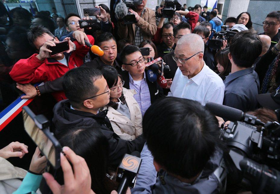 國民黨主席吳敦義(白衣者)上午在中央黨部門口,與不滿不分區名單而靜坐的台北市議員羅智強(左下)等人溝通。記者林澔一/攝影