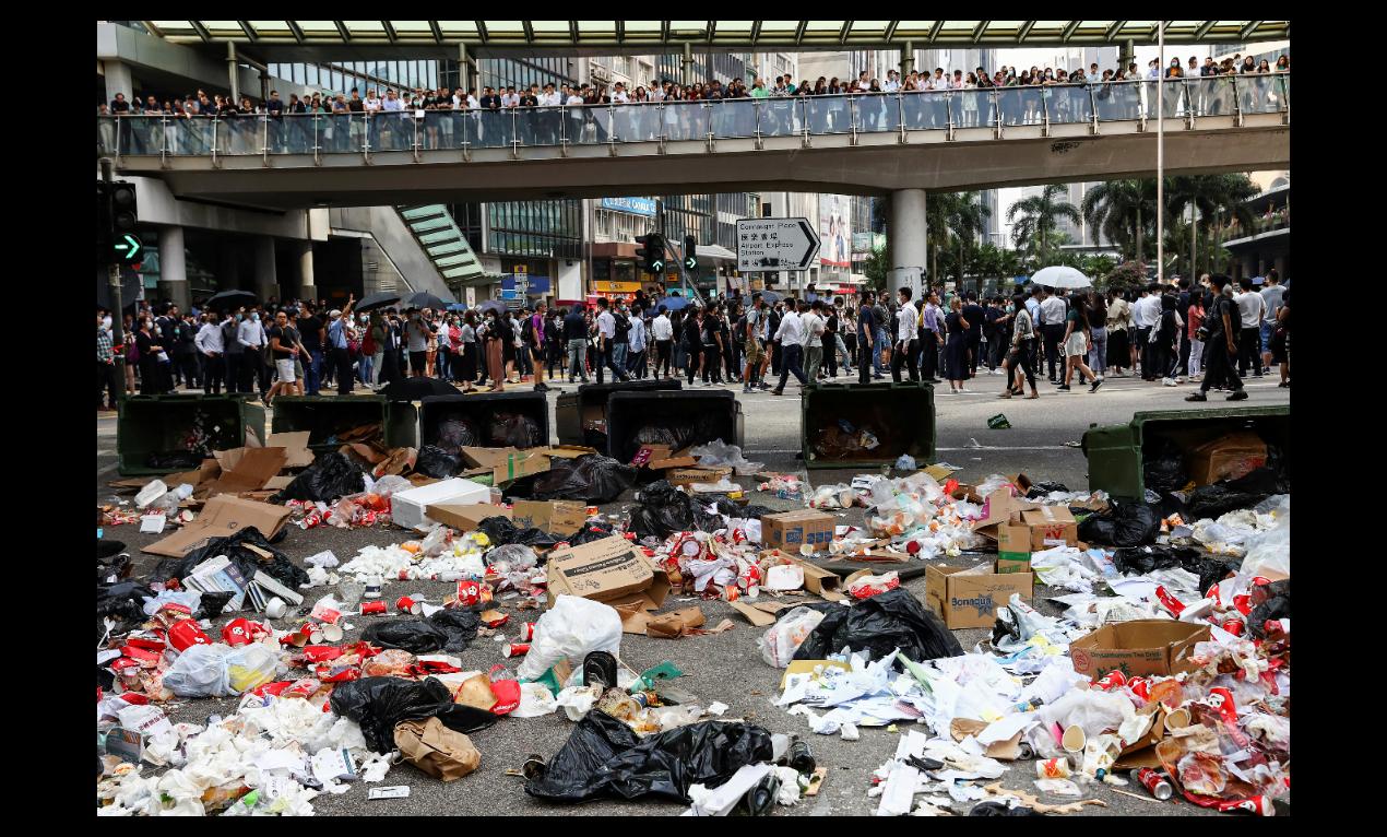 香港情勢近日急轉直下,圖為14日香港市區街景,抗議人士將垃圾桶推至馬路上並將垃圾...