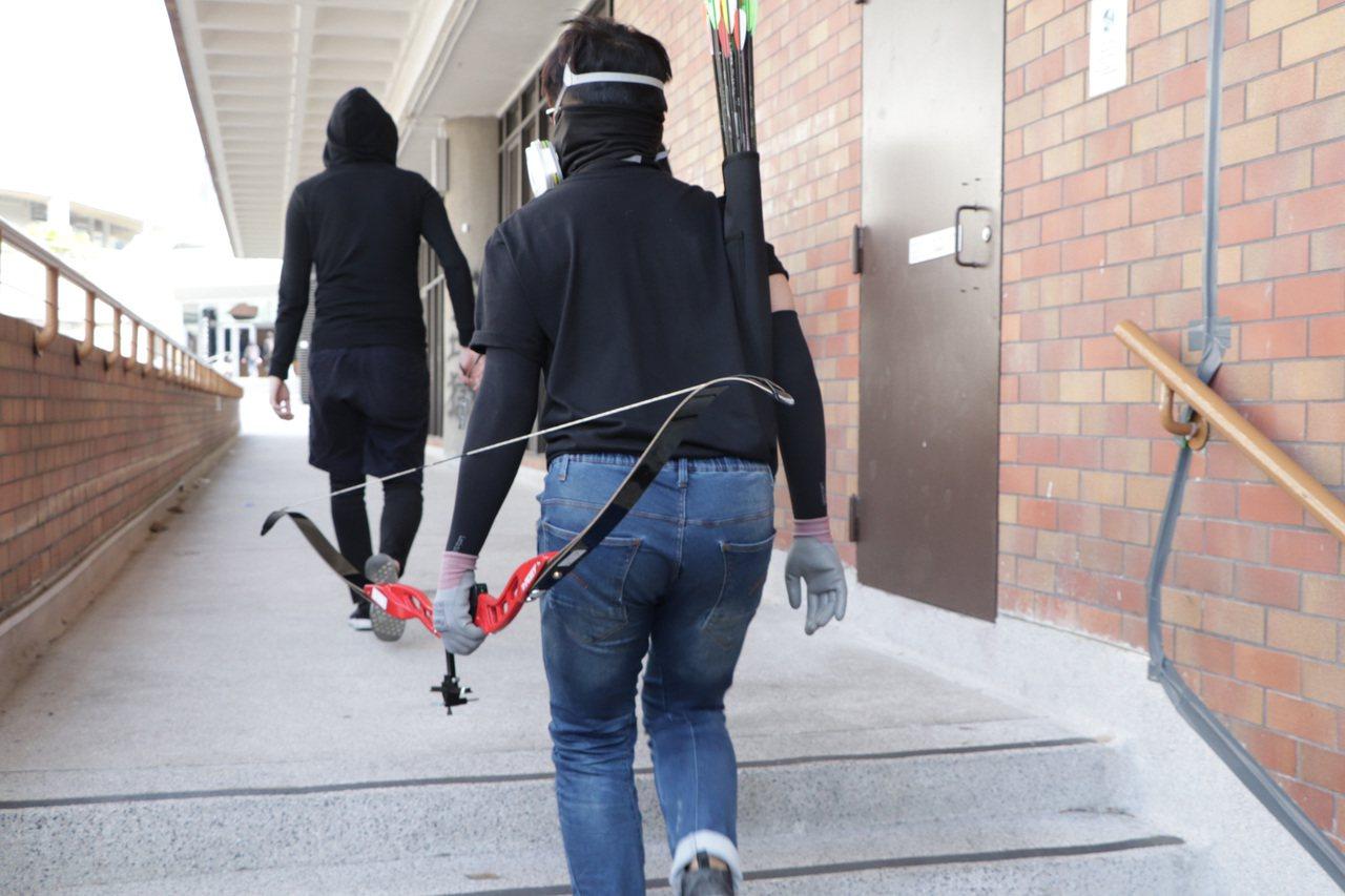 香港理工大學抗爭學生,14日持弓箭對付防暴警察。(中央社)