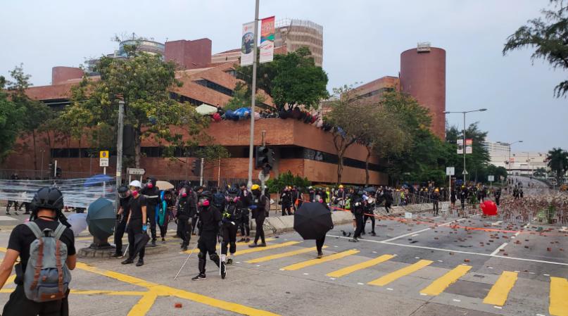 示威者在香港理大附近以磚頭堵路,防暴警到場戒備。(星島網)