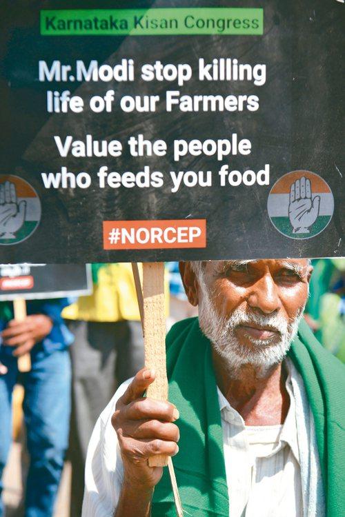 一名社運人士4日在印度班加羅爾市舉牌,抗議印度總理莫迪打算簽署RCEP,標語寫著...