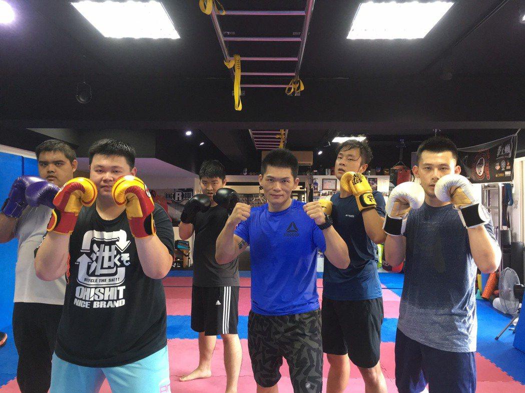 拳士瘋健身教練黃文祺(中藍衣者),指導學員訓練,強健身心。圖/拳士瘋健身教練黃文...