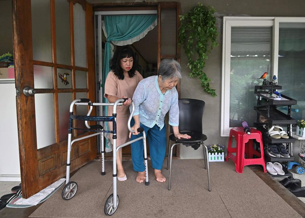 蘇瑪彭(後)平常要幫89歲且無法獨自行走的婆婆(前)如廁、洗澡和更衣。(法新社)