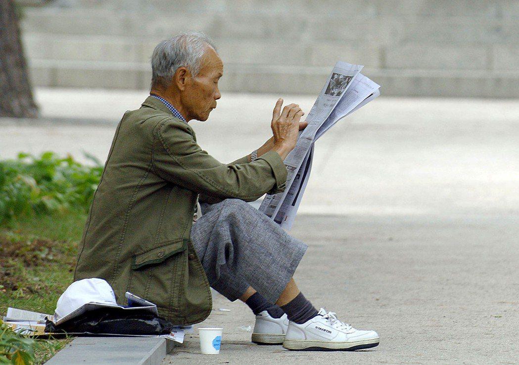 一名南韓老人在首爾的公園看報紙。南韓社會期望家庭自行照顧長者,政府提供的協助很少...