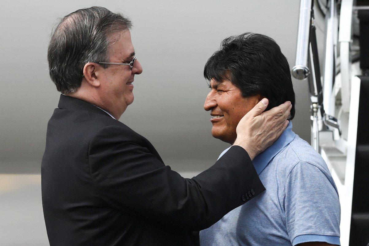 墨國外長厄伯拉特(左)12日在停機坪歡迎玻利維亞前總統莫拉萊斯。 (路透)