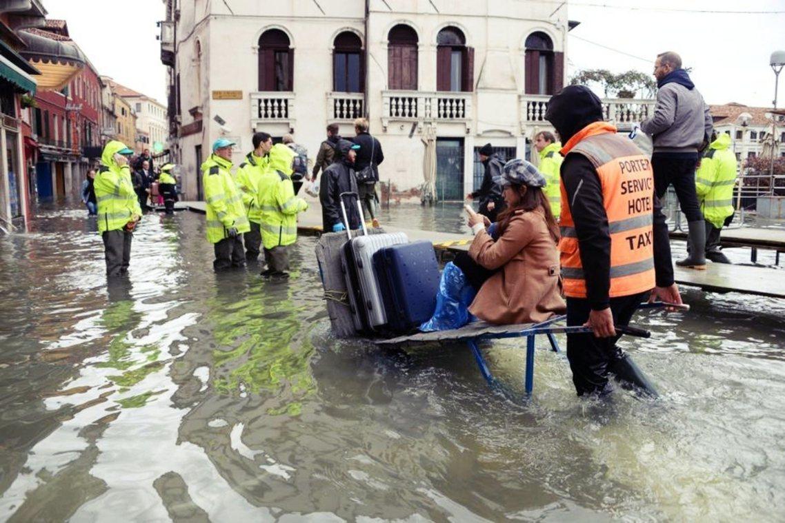 15日,大潮再來。有遊客坐著木板推車,載著行李涉水而過。 圖/歐新社