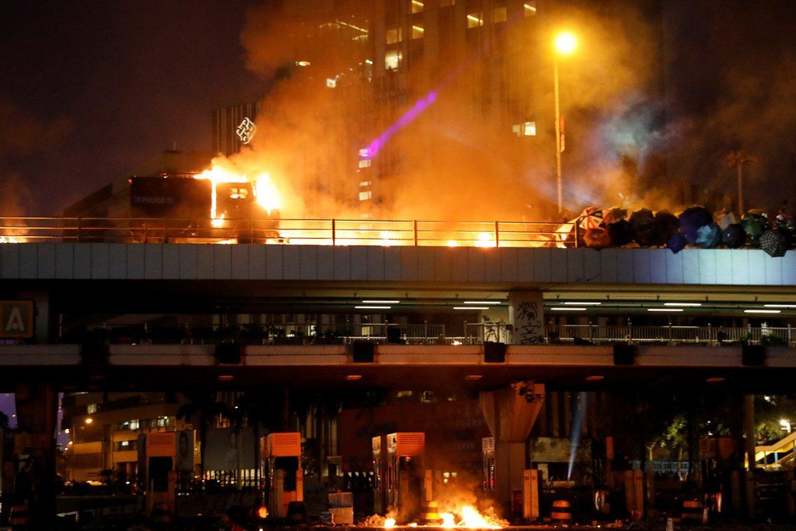 一輛警隊的輪式裝甲車,在催淚瓦斯與鎮暴彈的射擊掩護下,試圖從暢運道的行車天橋「強...