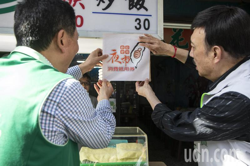 新北市議員陳啟能(左起)與立委余天,今到三重文化北路夜市為攤商業者貼上夜市消費抵用券。記者王敏旭/攝影