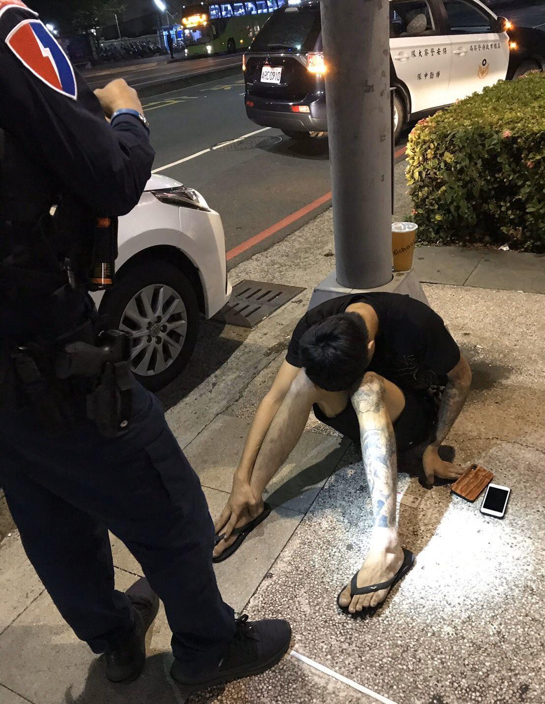 李姓男子遇警攔查,佯裝癲癇發作,癱坐地上。記者林保光/翻攝