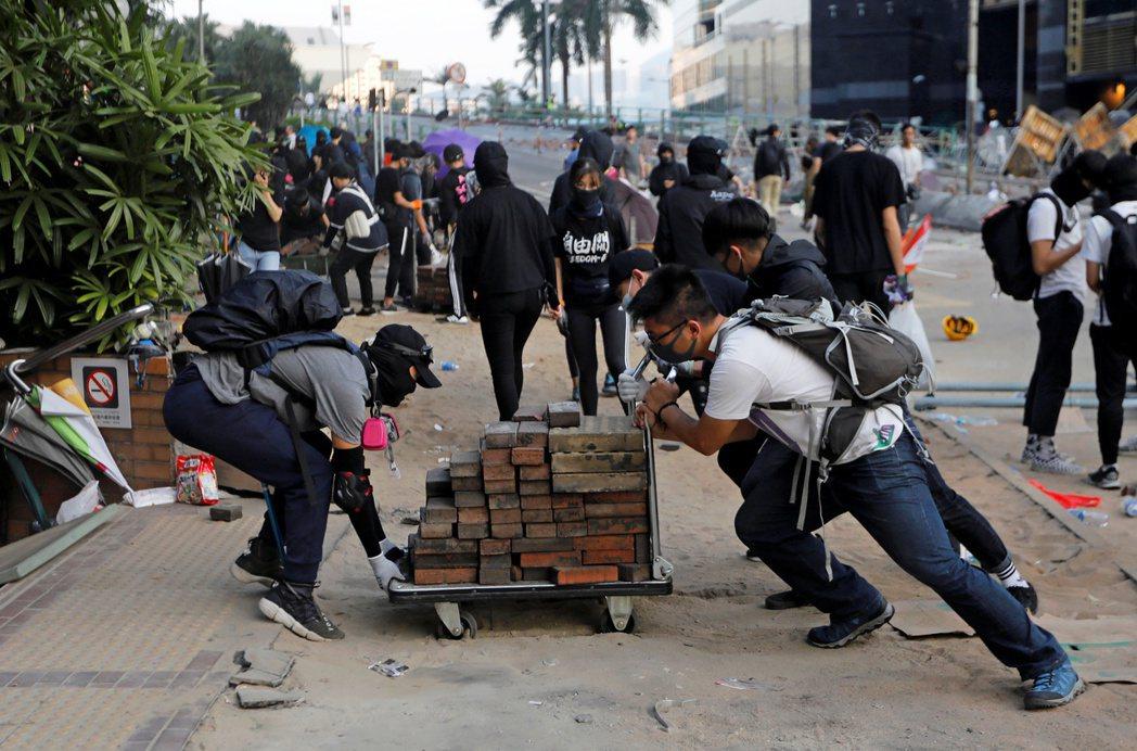 示威抗議者在香港理工大學用推車運輸磚塊與警察對抗。路透