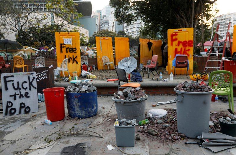 示威人士用桶子和磚塊石頭,在香港理工大學道路設置路障。 (路透)