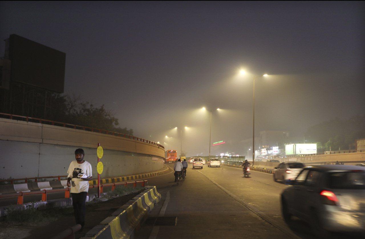 印度霧霾情況嚴重,入夜後的天空仍一片慘灰。 (美聯社)