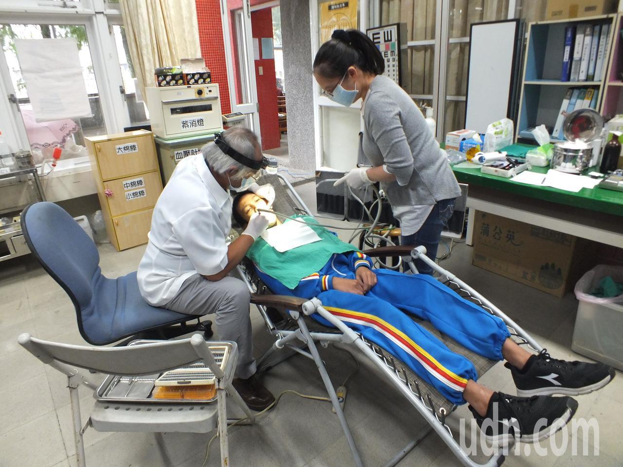 牙醫吳健民在巡迴醫療時,必須克服場地限制,自備躺椅、耗材、氣動幫浦等,為學童治療...