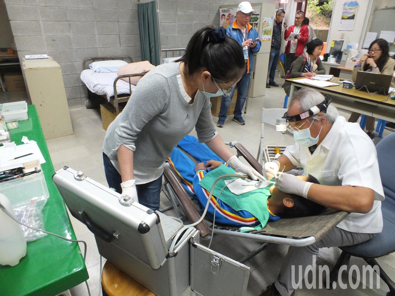 牙醫師吳健民(右)在巡迴醫療時,必須克服場地限制,自備躺椅、耗材、氣動幫浦等,為...