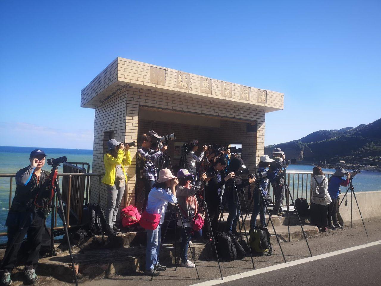 今天上午天氣非常好,十三層陰陽海前公車站牌已擠滿大批攝影愛好者,搶拍美景。圖/張...