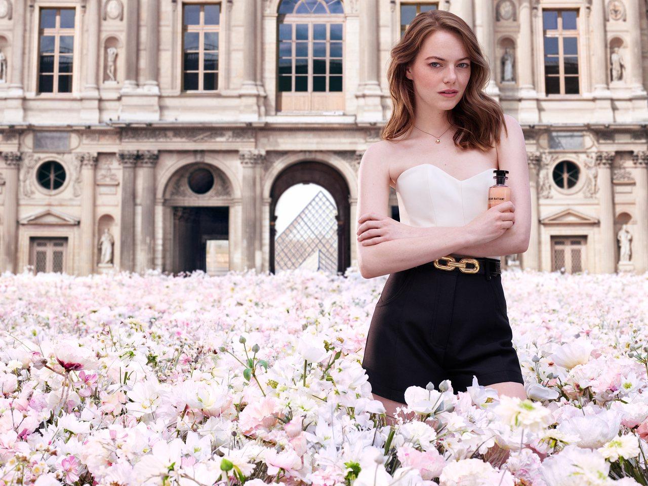 艾瑪史東置身在巴黎羅浮宮前的花海中,拍攝路易威登香水形象廣告。圖/LV提供