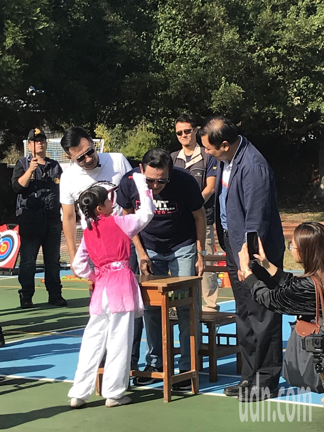 前總統馬英九與學生一起玩趣味競賽,小朋友拿彩色筆在馬臉上「塗鴉」,相當趣味。記者...