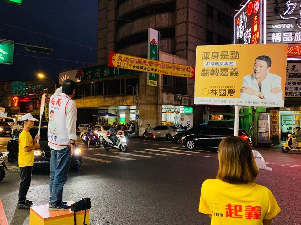嘉義縣無黨籍立委參選人林國慶站在路口,向鄉親揮手拜票。圖/取自林國慶臉書