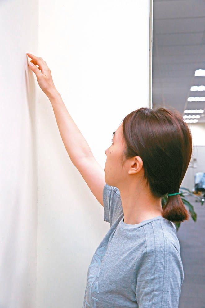 爬牆運動面向牆壁站立,手指觸摸牆壁,慢慢向上爬行並逐漸伸直手臂,到不能向上為...