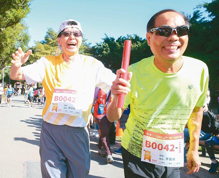 器官捐贈接力路跑昨在大安森林公園舉行,器捐中心董事長李伯璋(左)交棒給腎臟移植受...