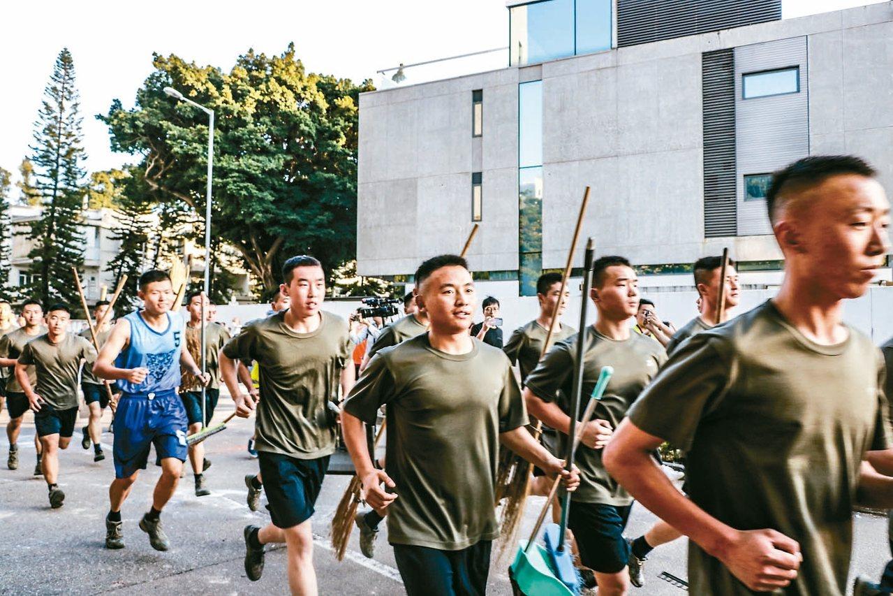 解放軍駐港部隊穿便服跑步出勤,協助清除示威者設置的路障和地面磚塊。 (中通社)