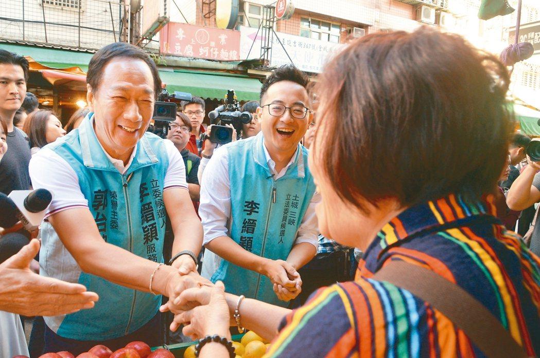 鴻海集團創辦人郭台銘(左)帶著李縉穎(中)在新北市土城區的市場拜票,受選民熱烈歡...