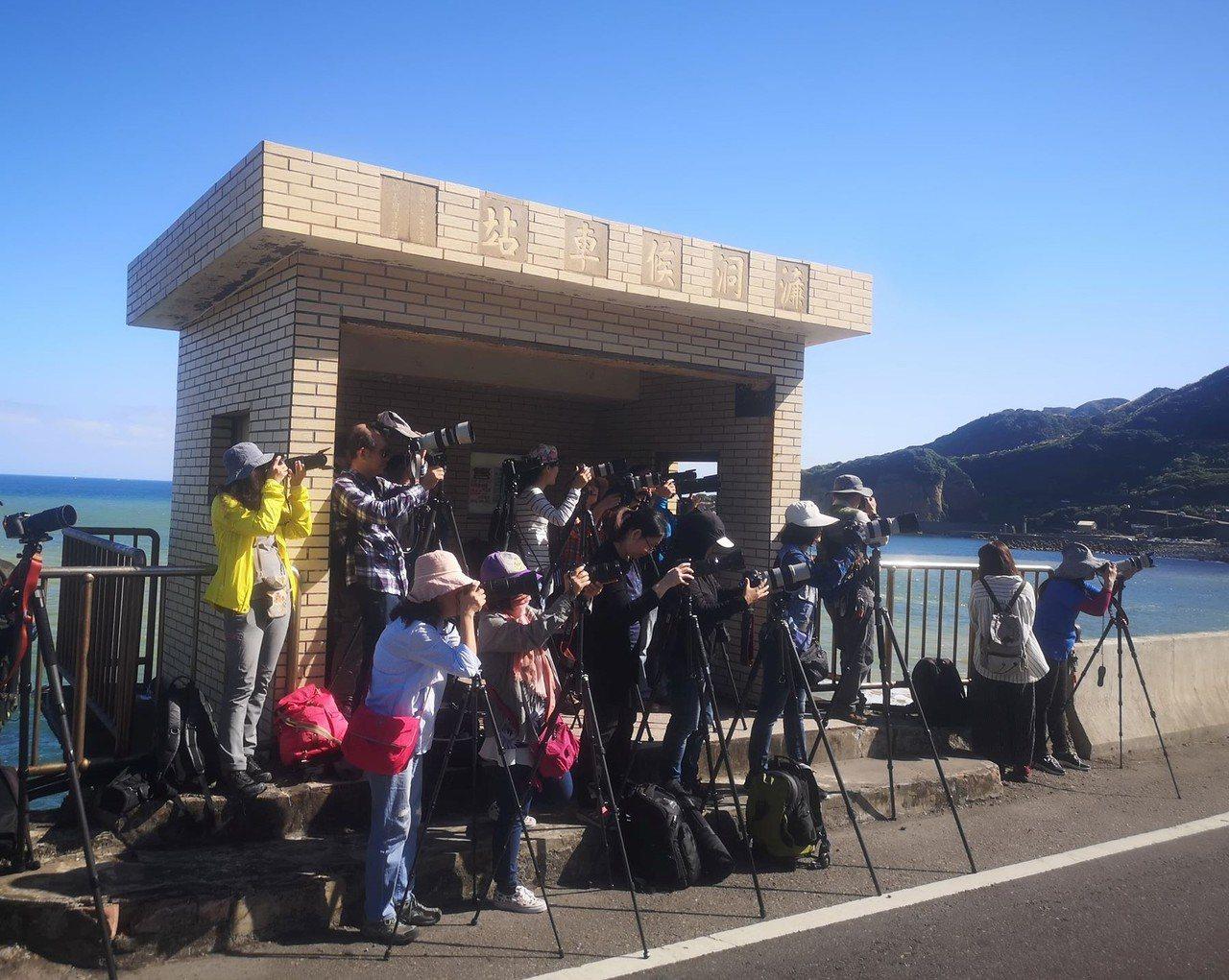 十三層遺址前方陰陽海前公車站牌,擠滿大批攝影愛好者拍攝。圖/張隆提供