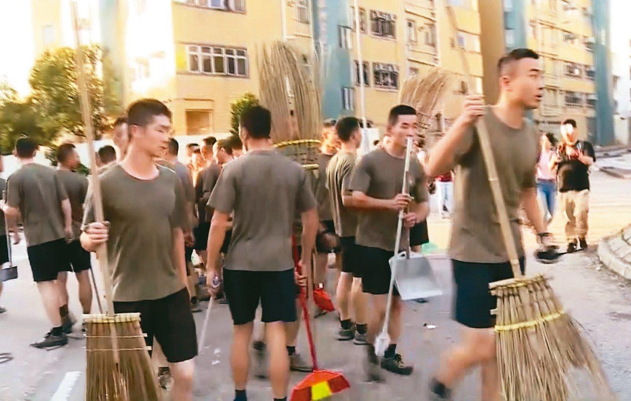 駐港解放軍16日穿著便服、拿著掃把在香港街頭清除路障。 美聯社