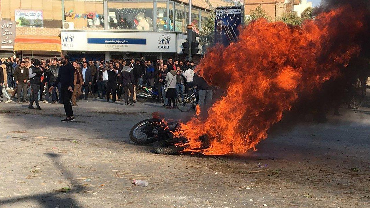 伊朗伊斯法罕街頭16日有機車遭示威者縱火焚燒,抗議油價高漲,民眾駐足圍觀。法新社