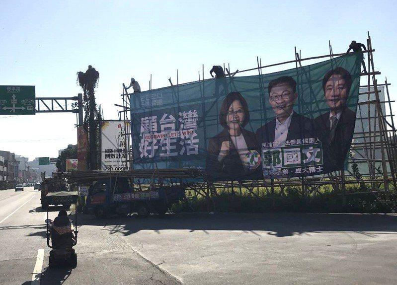 蔡賴配成真 ,民進黨台南第二選區立委參選人郭國文看板立即「換新裝」,圖為在台南佳里區看板正更換情形。圖/郭國文服務處提供