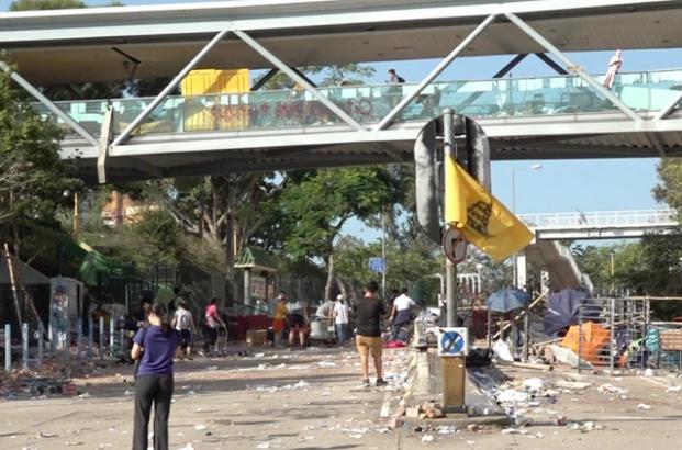 一批民眾到香港城大附近清理路障和雜物,有防暴警察在場戒備。(香港電台)