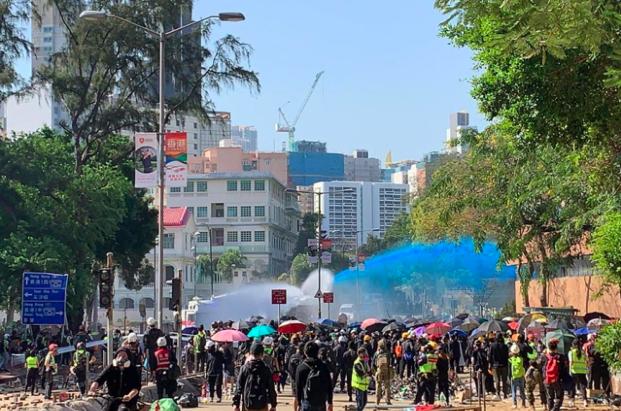 港警於理大對開漆咸道南,出動兩輛水炮車驅散示威者。(香港電台)