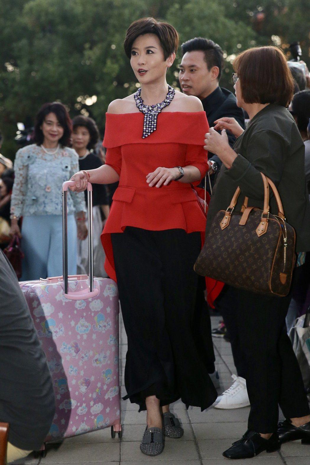 特別返台參與婚宴的寇乃馨則以紅色荷葉邊上衣搭配黑色寬褲現身,並配戴藍、紫色系的項...