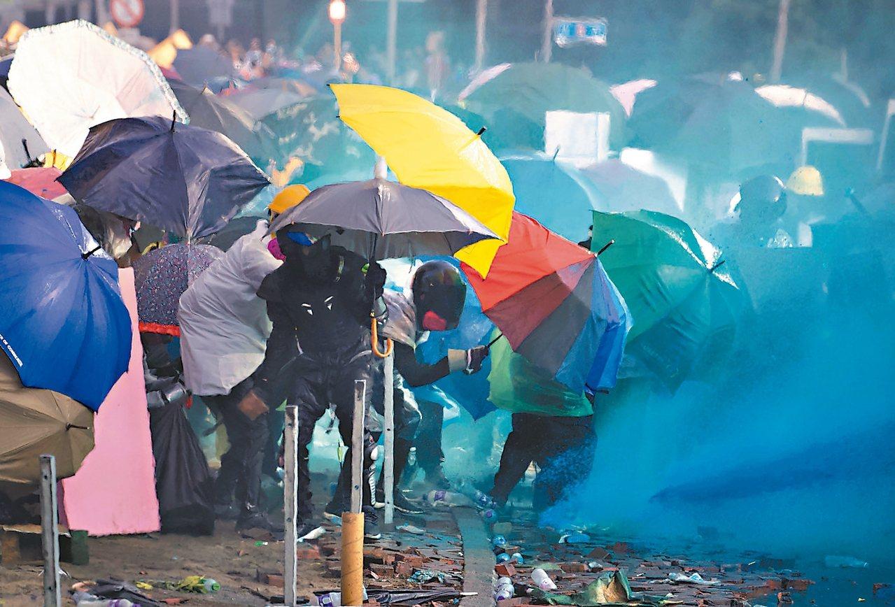 港警昨在理大外發射藍色水柱,試圖驅散示威者,示威者紛紛撐傘阻擋。 (美聯社)