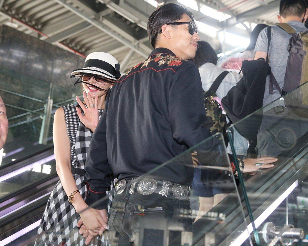 林志玲(左)與AKIRA (右)完成世紀婚禮後,抱著99朵玫瑰花現身台南高鐵。記...