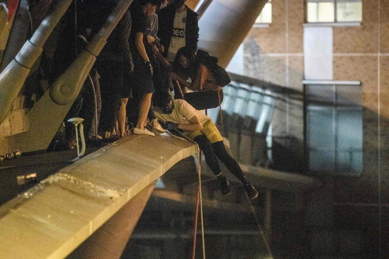 理大校園内有數人從高處攀繩索打算離開。法新社