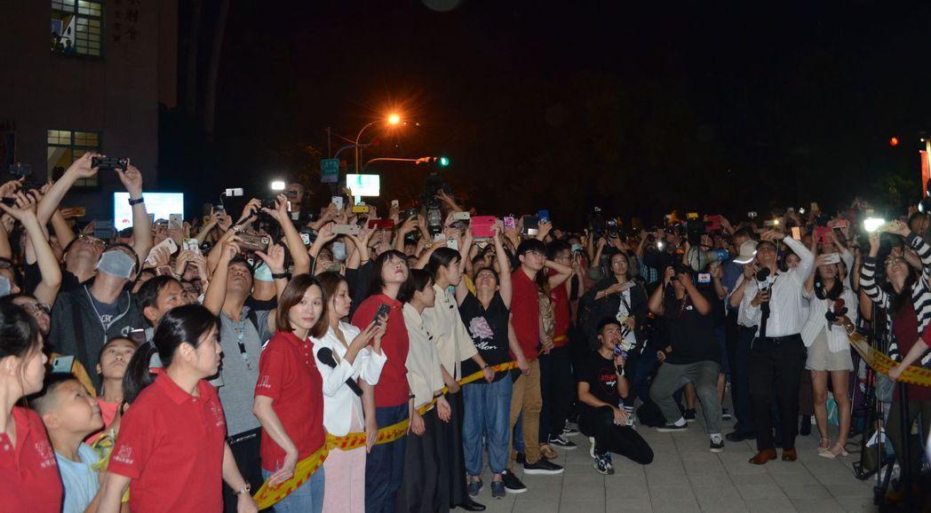 民眾高舉手機錄下新人在露臺上揮手的美麗鏡頭。  陳慧明 攝影