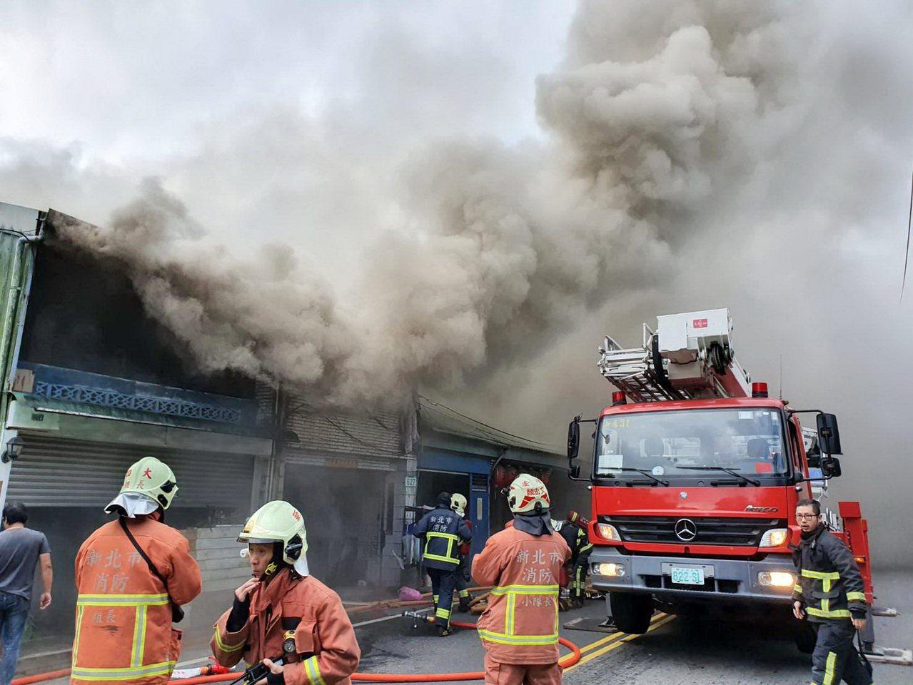 新北市新店區安康路3段一棟2層樓透天厝,18日發生火警。消防隊員在現場救出2人,...