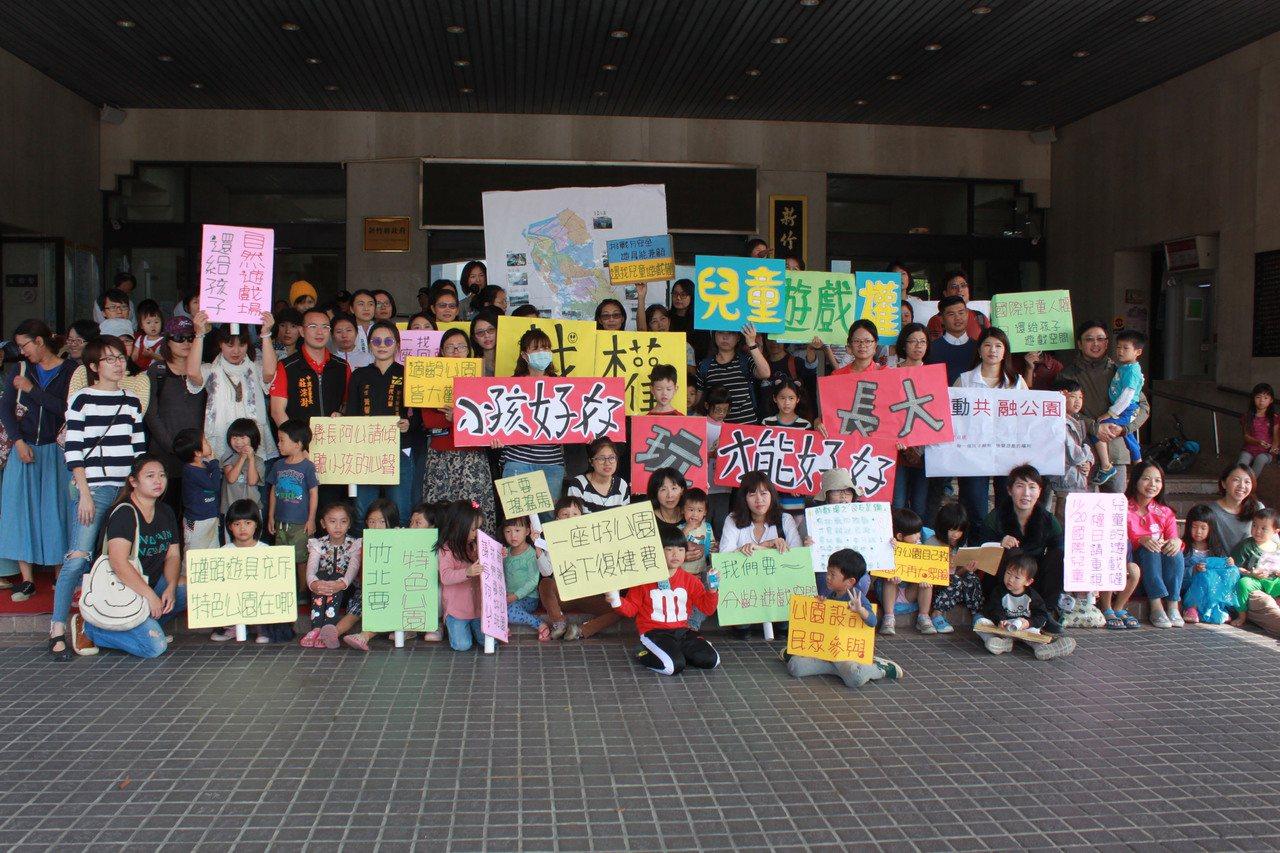 新竹縣30多位積極爭取兒童遊戲權的親子家庭今天一早到新竹縣府前開記者會。記者郭政...