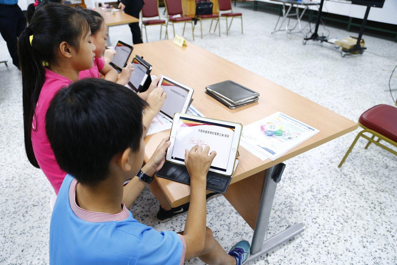 興展系統科技有限公司今天捐贈Labear行動教學系統,學童現場試用上手。圖/苗栗...